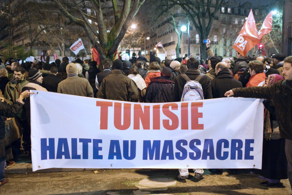 """People hold a banner reading """"Tunisia, stop massacre"""" during a demonstration against Tunisian President Zine El Abidine Ben Ali on January 11, 2011 in Paris. Anger over a government crackdown on protesters in Tunisia grew Tuesday as a union official said 50 were killed in three days of violence, more than double a toll issued by the interior ministry. AFP PHOTO LIONEL BONAVENTURE (Photo credit should read LIONEL BONAVENTURE/AFP/Getty Images)"""