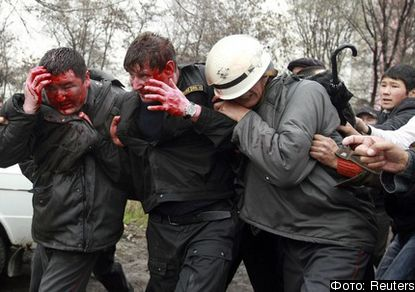 Injured policemen try to escape from anti-government demonstrators during clashes near the presidential administration in Bishkek April 7, 2010. Kyrgyz troops opened fire on anti-government protesters on Wednesday outside the offices where President Kurmanbek Bakiyev was sheltering from clashes that have killed dozens of people, a Reuters witness said.     REUTERS/Vladimir Pirogov (KYRGYZSTAN - Tags: POLITICS CIVIL UNREST)